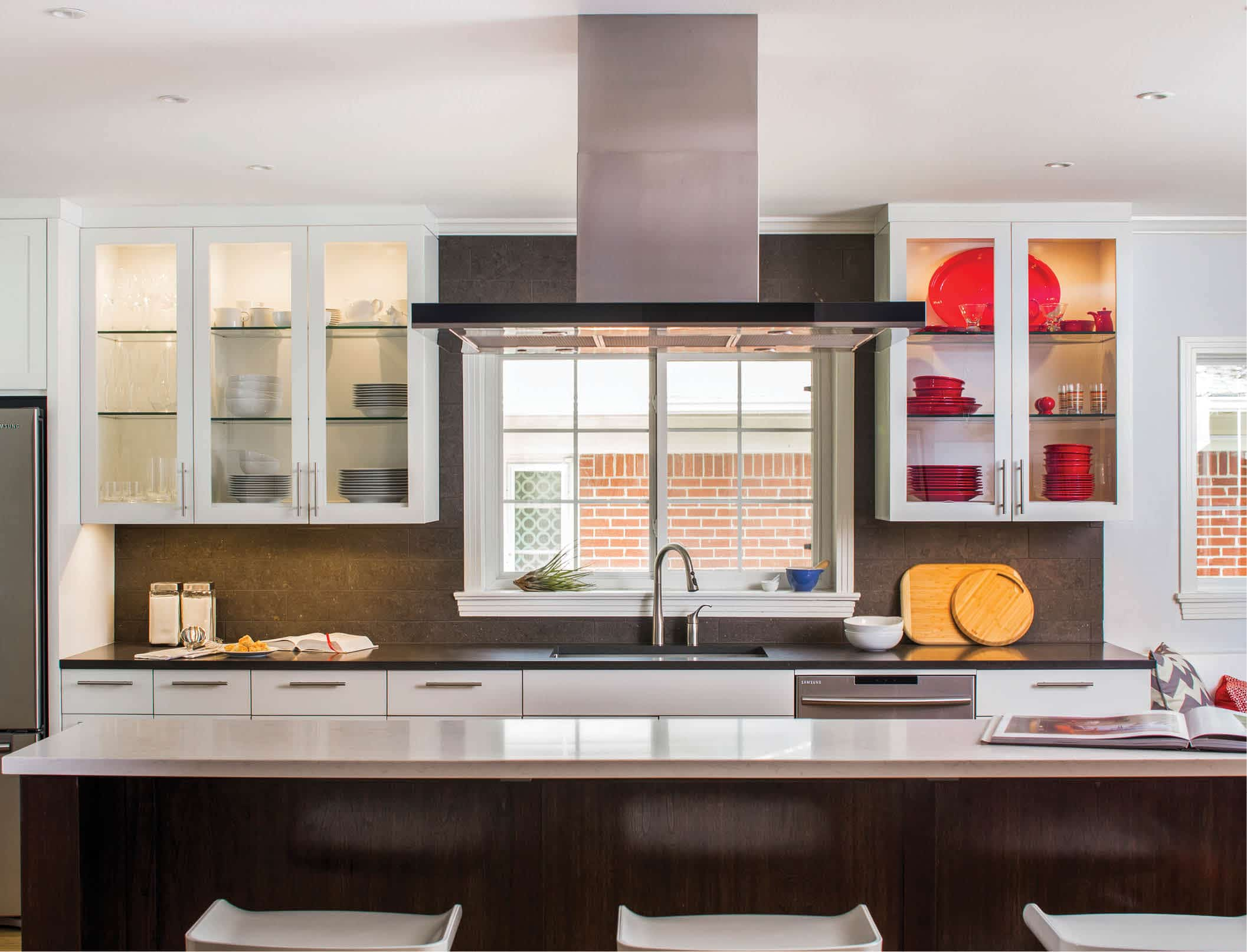 Dressed in walnut cabinetry with a light grey Caesarstone counter, the island provides a dramatic contrast to the white shaker style cabinetry and dark grey Caesarstone counters wrapping the perimeter of this new kitchen. Work by CG&S Design-Build. Photo: Tre Dunham