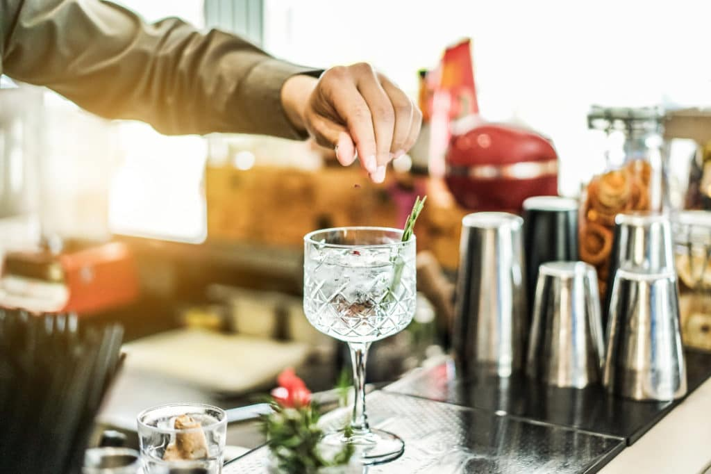 Bartender preparing cocktail with gin , rosemary and pink pepper inside bar - Soft focus on top crystal glass - Lifestyle , nightlife , drinking and entertainment concept - Contrast retro filter
