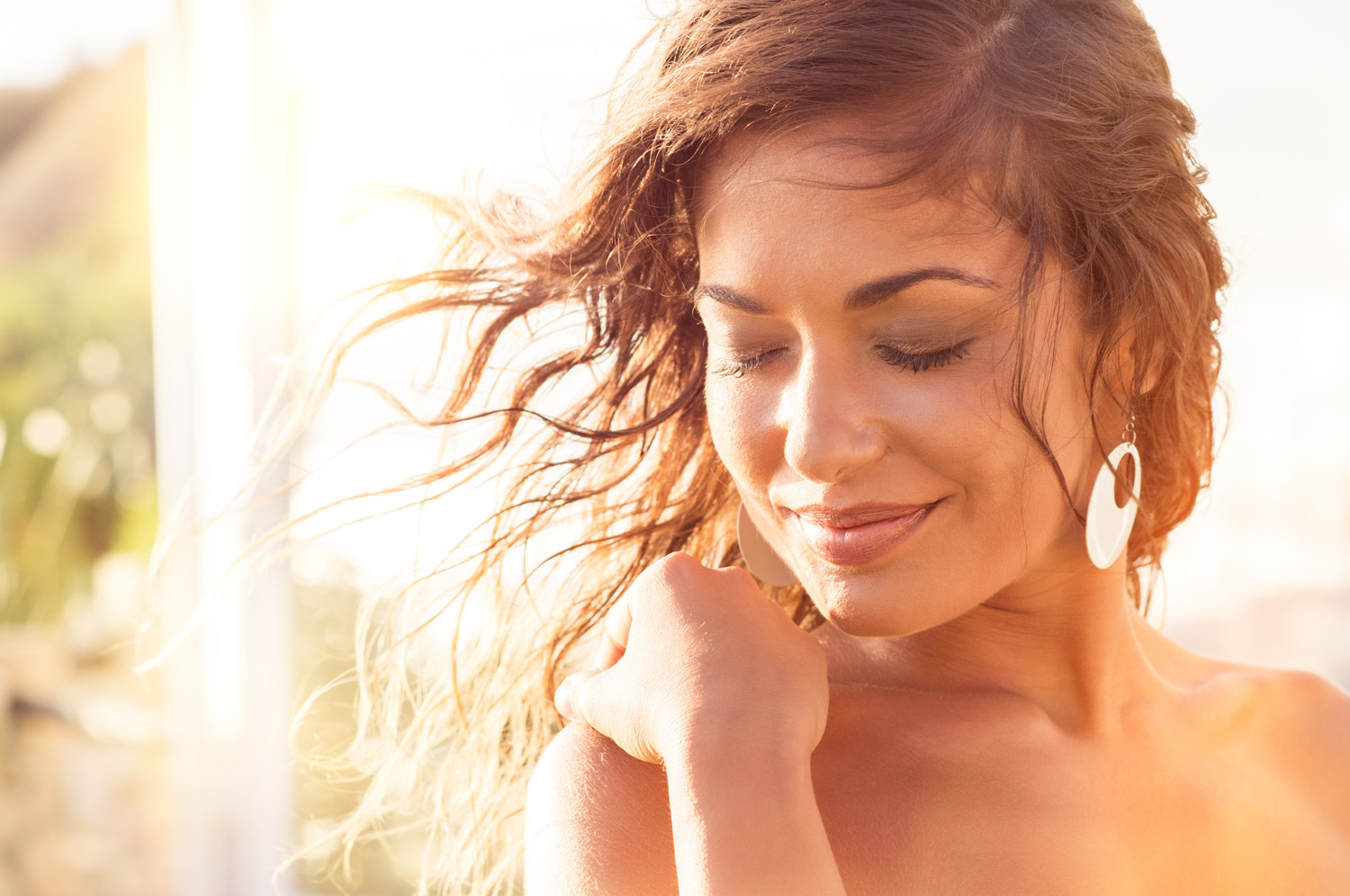 Closeup Of Smiling Young Woman With Eyes Closed At Sunset